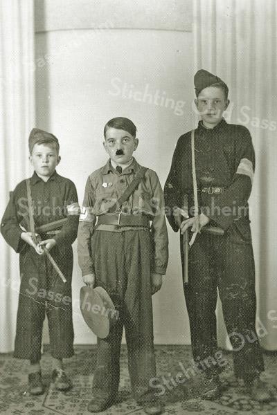 F1101 <br /> Bevrijding. Rechts staat Aad van Rijn, in het midden staat 'Hitler' (Henk van Rijn) en links staat Piet van Rijn. <br /> Adriaan (Aad) en Piet, gekleed als BS'ers, brachten 'Hitler' op. Henk draagt de koppelriem van meester Driessen (reserve-kapitein bij de artillerie en als zodanig in 1939/1940 ook gemobiliseerd), die op Rusthofflaan nr. 7 woonde. Foto: augustus 1945.