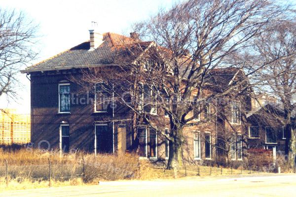 F0238 <br /> De bekende dubbelvilla Twin's Home aan de Hoofdstraat. Op de achtergrond staan de kratten van de kistenfabriek M.Bakker en Zn. Het gebouw rechts was ingericht als kantoor, daarachter stond de bollenschuur van Fred de Meulder, die later bij de kistenfabriek is getrokken. In het linkerdeel van Twin's Home woonde in de jaren '30-'40 de fam. Van der Weijden. In het rechterdeel woonde de fam. Van der Voort. Twin's Home is in 1991 afgebroken, maar de monumentale rode beuken zijn blijven staan.  Foto: 1983.