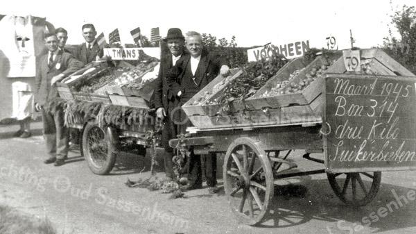 F0919 <br /> Optocht met groenten en fruit na de bevrijding. Vooraan een handkar met bord waarop suikerbieten verkrijgbaar worden gesteld zoals tijdens de laatste oorlogsjaren. Daarachter een motorbakfiets met volop groenten en fruit na de bevrijding. V.l.n.r.: Willem Nederstigt, Wim van der Bent, Leen van Klaveren, Piet de Waard en David Schaik. Foto: 1945.