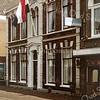 F1550<br /> Voormalig hervormde pastorie aan de Hoofdstraat in Sassenheim, gebouwd in 1873 en sinds 1998 rijksmonument. Nu het woonhuis van de fam. Langeveld. Uiterst rechts de herenmodezaak van Melman, nu Melman Business & Casuals.