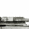 F0680c <br /> Links de romp van molen De Nijverheid van Speelman, met andere bedrijfsgebouwen. Langs de heg liep het Speelmanlaantje, dat uitkwam op de Hoofdstraat tegenover de Zuiderstraat. De foto is een detail van een persfoto van een bloemencorso t.g.v. het 25-jarig regeringsjubileum van koningin Wilhelmina in 1923.
