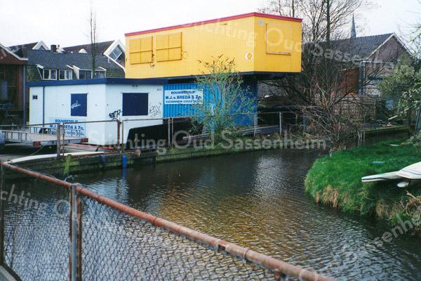 F0326 <br /> Een aftakking van de Sassenheimervaart, foto genomen vanaf het terrein van de Kringloopwinkel aan de Bijweglaan. Uiterst links de werkplaats van bouwbedrijf M.J. van Breda & Zn. met de containers op de voorgrond. Daarboven twee woonhuizen aan de Kerklaan, van achteren gezien. Daar bovenuit de puntgevels van de bibliotheek. De schuur rechts behoort bij de Kunstaardewerkfabriek Velsen, met daarboven de spits van de Dorpskerk. Foto: 1998.