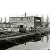 F2664<br /> De bollenschuur en het kantoor van de Gebr. Doornbosch & Co. aan de Postwijkkade wordt afgebroken. Op deze plek zijn in 1984 huizen van de Postwijk gebouwd. Op de achtergrond huizen aan de Zandslootkade