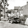 F1616 <br /> Jan van der Krogt ventte de melk uit bij melkboer Breedijk aan de Kerklaan. Hij zit hier op de ponywagen in de Kerklaan. Op de achtergrond 't Bruine Paard aan de Hoofdstraat. Rechts de twee woonhuizen van de fam. Van Rijn; links woonde de fam. Koning.  Het hoge pand rechts is de Kunstaardewerkfabriek Velsen. Foto: ca. 1950.