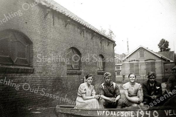 F1594 <br /> De koeienstal van de fam. K. Drost aan de Kastanjelaan. Links zit Dien Drost naast A. de Roo. Verder Pleun Drost en naast haar W. Buntsma. Op de achtergrond de zijgevel van de School met den Bijbel aan de Concordiastraat. Foto:1950.