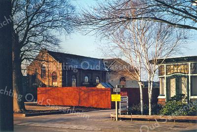 F0094 <br /> De oude werkplaats van de kistenfabriek van M. Bakker aan de Hoofdstraat. De huisjes van de dames Rooza, die hier vóór stonden, zijn weggebroken. Duidelijk is te zien, dat de werkplaats een voormalige kerk is geweest. Het gebouw heeft van 1876 tot 1912 dienstgedaan als gereformeerde kerk. Het afgebakende terrein is in 2016 alweer enige jaren een tuin. Foto: 1998.