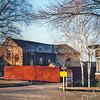 F0094 <br /> De oude werkplaats van de kistenfabriek van M. Bakker aan de Hoofdstraat. De huisjes van de dames Roosa, die hier vóór stonden, zijn weggebroken. Duidelijk is te zien, dat de werkplaats een voormalige kerk is geweest. Het gebouw heeft van 1876 tot 1912 dienstgedaan als gereformeerde kerk. Het afgebakende terrein is in 2016 alweer enige jaren een tuin. Foto: 1998.