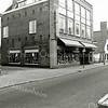 F1368 <br /> Links op de foto een gedeelte van het postkantoor aan de Hoofdstraat. Daarnaast het voormalige huis van dokter Hueber. Dit pand is daarna verbouwd tot winkel voor huishoudelijke artikelen van G. Lascaris, met links de inrit naar de werkplaats. Daarnaast staat het witte huisje van schilder Van Goeverden; daarnaast de kruidenierswinkel van Van Goeverden; de schilderswinkel en woonhuis van Vogelaar en de kruidenierswinkel van J. van der Klugt (voorheen Mathôt). Foto: jaren '