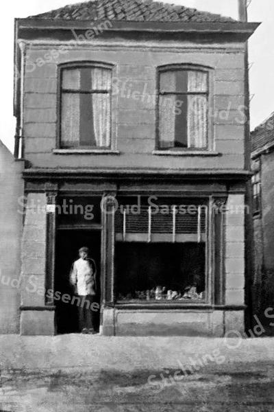 F0016 <br /> Van Lierop voor zijn winkel in fijne vleeswaren, kaas, boter etc. aan de Hoofdstraat. Later werd het de winkel van Nederstigt en daarna het Sassenheims Vloerenhuis. De reclamebordjes aan de muur ontbreken en Van Lierop  is jonger. Het pand had huisnummering 203 (oude nummering). Foto: ca. 1920.