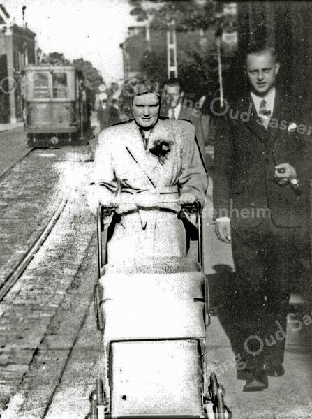 F0259 <br /> Het echtpaar G. Beijk-Vermin wandelend langs de Hoofdstraat. In de wagen zit Aad Beijk (A.A.J. Beijk). Tussen het echtpaar door zien we één van de gebruikelijke masten voor de elektrische tram. De foto is genomen in noordelijke richting ter hoogte van park Rusthoff. Vermoedelijk staat de tram stil bij de halte. Foto: 1947.