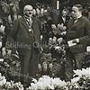 F3219<br /> De opening van de bloemententoonstelling 'De aangeklede Bloem'  in het jaar 1933 door burgemeester J.P.Gouverneur.<br /> Links staat dhr W. Warnaar, dan burg. J.P. Gouverneur;  waarschijnlijk dhr. Westerbeek, dan Jaap Wijntjes; K.W. van Breda en uiterst rechts Arie v.d. Voet.