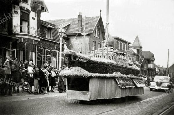 F0365 <br /> Eerste bloemencorso in 1948. De tramrails liggen er nog, die zijn in 1950/51 opgebroken. De foto is genomen ter hoogte van de Hoekstraat. Links de villa Siwah, dan villa Via Recta, de bollenschuur van Scheffers & Kroes N.V. en het torentje van villa Hestia. Verder nog het pand Bijdorp; uiterst rechts het gemeentehuis. Het schip stelt voor de Westerdam van de Holland-Amerika Lijn waarmee de eerste exportbollen na de oorlog naar de Verenigde Staten werden vervoerd.