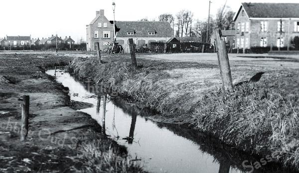 F3965<br /> Op deze foto is het tracé van de Parklaan nog toekomst. De brug over de Sassenheimervaart is er nog niet: we zien een onverharde weg vanaf de Kerklaan. Deze maakt nog de rechterbocht naar de Iepenlaan (Adelborst van Leeuwenlaan). <br /> Het muurtje van het perkje op de hoek van A. Van Leeuwenlaan (pijltje) is net te zien, daarachter de bollenschuur van de fa. L. Kruijff en op de achtergrond het gebouw van gemeentewerken. Links de huizen van de wijk Ter Leede.