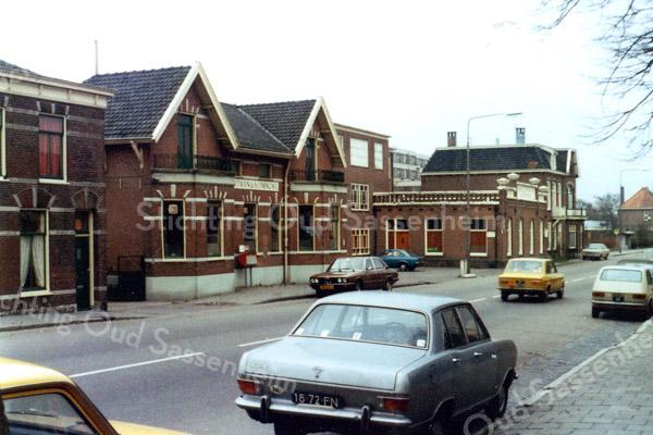 De bollenbedrijven van Baartman & Koning en van Van Zonneveld & Philippo. Beide bedrijven , gelegen aan de Hoofdstraat, waren een begrip voor Sassenheim. Op het dak van de schuur van Z&P werd door een sirene (de zgn. fluit) het begin en einde van de schaft- en werktijden aangegeven. Dat geluid was zó hard, dat het in de wijde omgeving te horen was. Beide panden en het woonhuis links van de laatste bewoner Klaas Tukker werden in 1976/77 gesloopt.  Foto: ca. 1975.