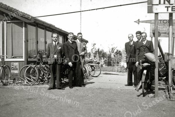 F0395 <br /> Foto genomen in begin jaren '40 bij de koffietent De Uiver aan de Rijksstraatweg, eigendom van de fam. Van Zoen. Links staat Piet van Zoen, daarnaast Toon Kort van de Kerklaan, de derde is Cor Verbeek. Links naast de paal, achter de fiets staat Piet Overvliet. Foto: begin jaren '40.