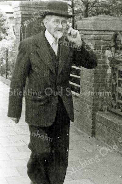 F2697<br /> De heer J.H. Blom (Jan)  (1875-1967). Hij was de vader van dhr. Piet Blom. Hij woonde in een pand aan de Hoofdstraat waar tot voor kort de Digros was gevestigd. Blom loopt hier over de Hoofdstraat langs het monumentale hek van de St. Pancratiuskerk.