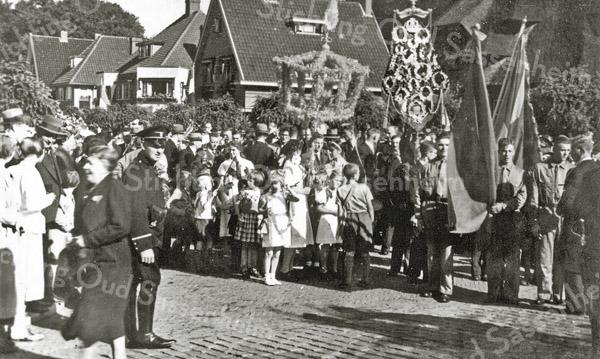 F0922 <br /> 40-jarig kroningsfeest van koningin Wilhelmina. Tweede man van links (met hoed) is Chris van der Voort. Daarvóór politieagent H.G.A. van der Laan. In de optocht wordt een kroon van bloemen meegevoerd en een vaandel van harmonievereniging Crescendo, met portretten van Wilhelmina. Links naast de linker vlag staat Leen van Klaveren, lid van de B.B. De tweede man van rechts is Kees Dorsman. Locatie: vóór het voormalige gemeentehuis (nu Sikkens Experience Center). Foto: 1938.