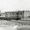 F1366b <br /> Het voormalige kantoor en de voormalige bollenschuur van de fa. Speelman aan de Hoofdstraat. N.V. Mecanorma-Polyvroom is er nu gevestigd, een firma in onder andere afwrijfletters. Op de voorgrond de aanleg van de Koetsiersweg in 1985. Alle gebouwen van Speelman werden tot de sloop in 1990 door de gemeente verhuurd.