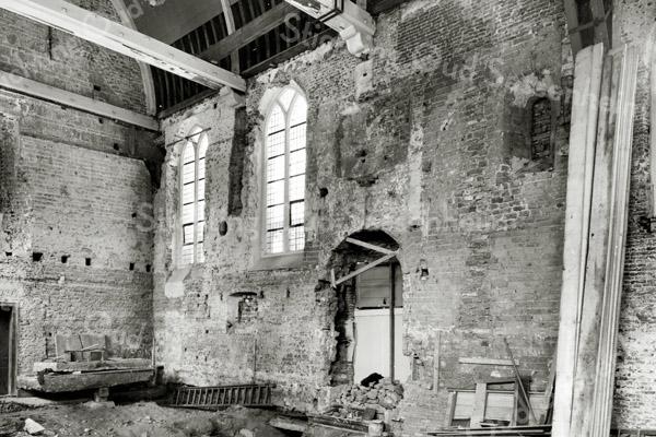 F0134 <br /> De restauratie van de Ned.-herv. kerk (Dorpskerk) vanaf 1971-1973. Te zien is de noordwand, waar de twee gotische ramen werden vervangen door de veel kleinere romaanse ramen. Rechts op de foto is het romaanse raam te zien, dat tevoorschijn is gekomen van onder het stucwerk. Links van de deur is ook een romaans raam te zien.   Foto: 1973.