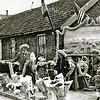 F1957<br /> Verkoop van bloemen en slingers. Op de achtergrond een rij oude arbeidershuisjes, die in de volksmond 'de Zevenhuizen' werden genoemd. Deze stonden in Sassenheim-noord ter hoogte van de Merelhof. Foto: voorjaar 1950.