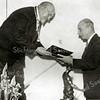 F3041<br /> Burgemeester J.P. Gouverneur biedt de heer A. M. Mees,<br /> directeur van Sikkens Lakfabrieken N.V., een 'ere-album'<br /> aan bij de opening van de fabriek op 1 december 1939.