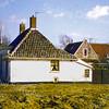 F0060 <br /> Het huis van de fam. L. Drost, een van de oudste huisjes van Sassenheim (1840). Thans (2016) woont hier W.J.N. van Hage. De foto is genomen na de afbraak van de huizen benoorden de Zuiderstraat. Op deze foto is de zijkant van het huisje goed in beeld en toont ook het pand van vader Thijs Drost, de bekende melkboer. Hij is later opgevolgd door zijn zoon Koos Drost. Foto: 1978
