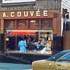 F0280 <br /> De slagerswinkel van A. Couvée, Hoofdstraat 218. De firma had twee winkels, deze vlakbij de J.P. Gouverneurlaan en één bij de Oude Post. De poort rechts van het pand was vroeger open: de toegang naar de Keerweerlaan. De bebouwing daarvan bestond uit twee blokken van elk vijf arbeiderswoningen; die zijn in 1963/64 gesloopt. Foto: ca. 1980.