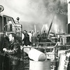 F3799<br /> De eerste van de twee grote Sikkensbranden, op 8 maart 1968, waarbij door alle brandweerkorpsen uit de omliggende gemeenten hulp werd verleend. We zien hier de brandweerwagen van Sassenheim, de DAF met als chauffeur Rinus Staring die informatie krijgt van Nol Janssen. Op de achtergrond zien we Gerard Koenen. Het nieuwe voertuig van Sikkens is helaas tijdens die brand verloren gegaan.