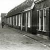 F0051 <br /> Zuiderstraat in vroeger jaren. De straat staat op het punt gesloopt te worden om plaats te maken voor nieuwbouw. Behalve de twee grotere huizen rechts vooraan bestaat de straat uit typische arbeiderswoningen van begin de vorige eeuw. Let op de klinkerstraat voor de ramen. De Zuiderstraat is gesloopt in 1975-1977. Foto: 1975.