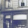 F0015 <br /> Van Lierop voor zijn winkel in fijne vleeswaren, kaas, boter etc. aan de Hoofdstraat 281. Hij liep met een verhoogde rechterschoen en bracht met een transportfiets (de mand voorop) de bestellingen rond. Later werd het de winkel van Nederstigt en daarna het Sassenheims Vloerenhuis. Let op de reclamebordjes aan de muur.