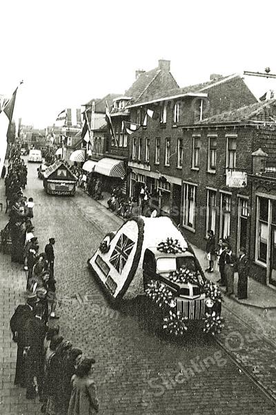 F1194 <br /> Het eerste bloemencorso in 1948. De wagen van de fa H. Verdegaal & Zn. rijdt door de Hoofdstraat ter hoogte van de melksalon van P. Langeveld sr. De straat is nog geplaveid met kinderhoofdjes en de tramrails liggen er nog. Dhr. Langeveld staat met zijn vrouw voor de melksalon. Verder zien we de winkels van Hendriksen en Lascaris. Foto: 1948.