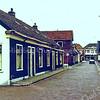F0295 <br /> De Kerklaan met de linkerzijde (zuidkant) en het gezicht op hotel-café-restaurant 't Bruine Paard aan de Hoofdstraat. In het eerste huis links woonde vrachtrijder P. Koning, dan schilder de Groot, metselaar Waasdorp, schilder Jaap v.d.Zwet en tuinman Hoekstra. De boerderij van W.van Rijn is hier al gesloopt. Daarna zien we de vroegere olieschuur van Jac. Oudshoorn, later opslagruimte van de aardewerkfabriek. De linkerkant is gesloopt in 1975. Rechts zien we nog een gedeelte van het woonhuis van de fam. Van Rijn en daarnaast de Kunstaardewerkfabriek Velsen. Foto: ca. 1975.