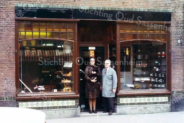 F0245 <br /> Een foto van het winkelpand van Cor Versluijs aan de Hoofdstraat nr. 210. Het pand is in 1977 overgenomen door MultiCopy (voorheen Printservice), die het in 1994 weer heeft verlaten om zich te vestigen aan de Koetsiersweg. Nu (2016) is bloemenzaak Royal Fleur Tetteroo erin gevestigd.  <br /> Cor Versluijs was een begrip in Sassenheim op het gebied van ijzerwaren. We zien hem hier samen met zijn tweede vrouw.  Foto: midden jaren '70.