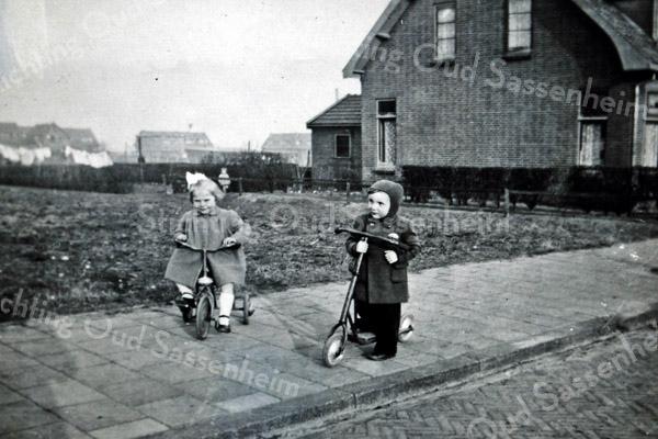 F3725<br /> Dit zijn Dick Wilbrink op de step en Joke Langeveld, buurmeisje.  Op de driewieler gefotografeerd eind jaren '40 in de Wilgenlaan, op de achtergrond zien we de huizen van de Lindenlaan en de Platanenlaan.