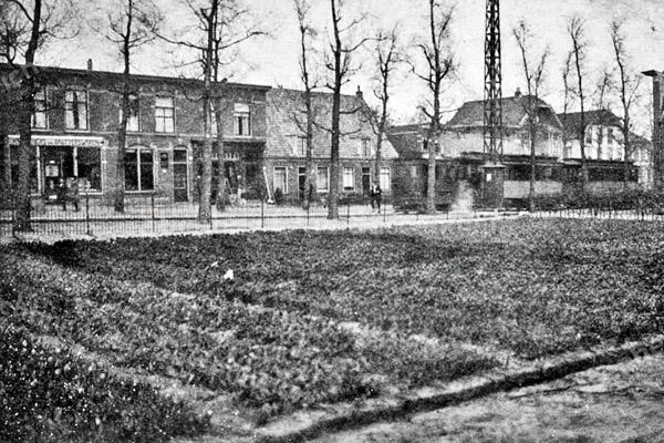F3769<br /> De stoomtram ter hoogte van de Zuilhofstraat met op de achtergrond de winkels van Eikelenboom (Koloniale en Grutterswaren) en de winkel in landbouw gereedschappen van Perfors.