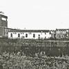 F0513 <br /> Sikkens Lakfabrieken met de toren voor de opslag van lak. Het gebouw links is de Pinorin-afdeling (verf voor huisschilders). De witte barak is het kantoor en laboratorium van Synthese (later verhuisd naar Katwijk). Rechts van de barak een gedeelte van het kantoor van Sikkens. Het hogere gebouw is de kantine en ontvangstruimte. Daarnaast de spoorhuisjes en het witte huisje van de oude mevr. Ciggaar, waar later Piet Spaan heeft gewoond, dat helemaal verbouwd is. Foto: ca. 1950.