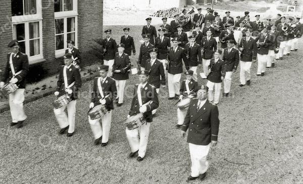 F0989 <br /> Harmonievereniging Crescendo poseert hier op 10 april 1954 in haar gloednieuwe uniform naast het Gereformeerde Jeugdhuis aan de Julianalaan op de plaats waar later eind jaren zeventig de Tussenzaal is gebouwd - later Blauwe Zaal genoemd. Het is vroeg in de avond en Crescendo staat klaar om af te marcheren voor een muzikale rondgang door het dorp. Diezelfde avond wordt ook nog een serenade gebracht aan meester A. den Haan van de Hervormde School, die 40 jaar onderwijzer is. In de eerste rij ziet u van links naar rechts: Henk Eigenbrood (?), Aad Luijk, Jan Broer, Willem Werk (slagwerkinstructeur). En in de tweede rij: Piet van Bladel, Jan Verhoef, Cees van der Heiden (jr.) en Wim Kruijswijk. De man rechts van de eerste rij is Rens van Duijn. Hij heeft de muzikale leiding; een tambour-maître is er dan nog niet.