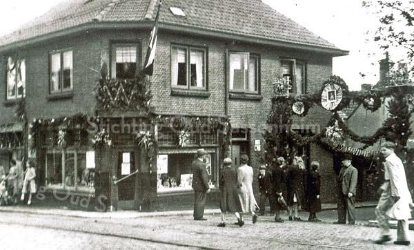 F0180 <br /> Koninginnedag 1948 of 1949. Het feest ging toen nog gepaard met erepoorten met het portret van de koningin, veel vlaggen en groenversiering. De foto is genomen aan de ingang van de Kastanjelaan. Helemaal links Arie Vos, de kolenboer (op de rug gezien), vierde van links de 'oude' J. van Diest (vader van mevr. Melman), zevende van links mevr. Van Duyvenbode, achtste van links A. van Duyvenbode, negende van links Karel van Tol, die later naar Nieuw-Zeeland is geëmigreerd.  Foto: 1948/49.
