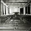 F0658 <br /> Het interieur van de Ned.-hervormde kerk omstreeks 1895. Ds. Daniël Johannes Marie Wüstenhoff was van 1891-1922 predikant in Sassenheim. De preekstoel stond toen onder het kleine raam aan de noordoostzijde. Let op de gasverlichting en de opstelling van de banken. De liturgieborden zijn nog steeds in gebruik.