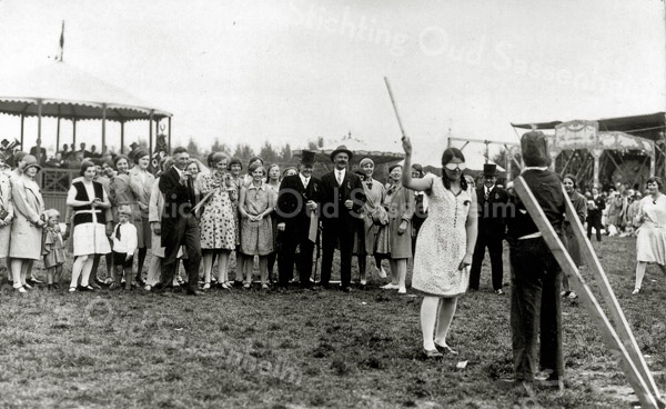 F0031 <br /> Oranjefeest in vroeger jaren. Het meisje met de stok is vermoedelijk een dochter van Piet Westerbeek sr. Zij is geblinddoekt en moet de pop zien te raken. Op de achtergrond kijken Klaas Oudshoorn (met hoed achterover) en naast hem schoenmaker Van Dam (met hoge hoed) lachend toe. Foto: ca. 1932