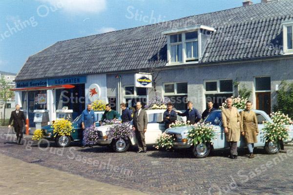 F1130 <br /> Garage H.G. van Santen in de Concordiastraat. Ter gelegenheid van het bloemencorso is een aantal auto's versierd. Henk van Santen (in kostuum) staat bij de middelste wagen. Bij de auto rechts staat links met stofjas Jan van Beek.