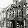 F0200<br /> Het raadhuis, gebouwd in 1870 onder burgemeester J.N.A. Bucaille is gelegen aan de Hoofdstraat. Links de hervormde pastorie en rechts het woonhuis van Koos Bakker. Achter het raam van het raadhuis zijn allerlei mededelingen aangeplakt. Sinds 1930 is de modezaak van Melman in het pand gevestigd,  tegenwoordig Hoofdstraat 226. Het karakteristieke torentje op het dak, het gemeentewapen daaronder en het bordes moesten ingevolge de koopovereenkomst met Melman verwijderd worden. Zie ook Sassenheim in oude ansichten van G. Verschoor en Sassenheim in grootmoeders tijd van drs. J. van Teylingen en H. Verhoef.  Foto: 1928.