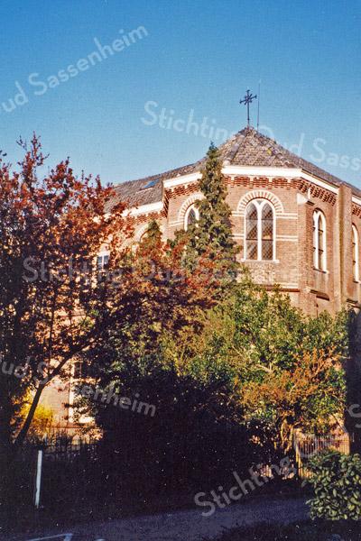 F0081 <br /> Nog een opname van Het Onderdak, het vroegere St. Annaklooster; nu meer van rechts gezien. Het fraaie, vooruitstekende kloostergedeelte verkeert nog in oorspronkelijke staat. Het hoekgedeelte dat boven de bomen uitsteekt (met het kruis er bovenop), was de kapel die door de zusters gebruikt werd. Dit gebouw werd in 1898 gebouwd door N. Huyg van de Oude Haven. De nieuwe meisjesschool werd geopend op 16 januari 1899. Foto: 1995. Zie ook F0080 en Sassenheim in grootmoeders tijd, pag. 35.