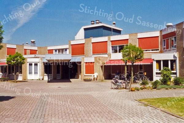 F0898a <br /> Foto van verzorgingshuis De Schutse aan de Jan van Brabantweg, gezien vanaf het plein aan de voorzijde. Het gebouw is in gebruik genomen in 1987 en afgebroken in 2011. Op deze plek is in 2015 het woon- en servicecentrum SassemBourg in gebruik genomen.<br /> Foto: 1998.
