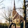 F0497 <br /> De Ned.-herv. kerk of Dorpskerk van Sassenheim aan de Hoofdstraat. Op de voorgrond het plein met een prachtig beeld De mandenophaler van Frans van der Veld, voorstellend een man met een mandenkarretje, waarop een stapel bollenmanden. Foto: 1999.