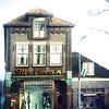 F0022 <br /> De damesmodezaak van Melman aan de Hoofdstraat, afgebroken in mei 1980. (Op deze plaats is in 2016 de damesmodewinkel van Van Uffelen.) Op het pand rechts staat de naam Barbara Pander. Dit pand is beter bekend als de viswinkel van Nic. Roos. Later is deze winkel verhuisd naar de hoek Hoofdstraat/J.P. Gouverneurlaan. Foto: ca. 1980.