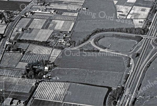 F3561<br /> Een luchtfoto van de Warmonderdam. Het motel Van der Valk was nog niet gebouwd. Rechtsonder naar -boven loopt de A44. De Rijksstraatweg loop aan de linkerkant. Foto:ca 1959