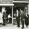 F2687<br /> Aan de Charbonlaan wordt de verbouwde fotozaak van firma Turk heropend. Voor de ingang ziet u Leo Turk met zijn vrouw en hun zoontje Gerard. Voor de etalage staan v.l.n.r.: dhr. Turk sr., zoon Kees en mevrouw Turk sr.