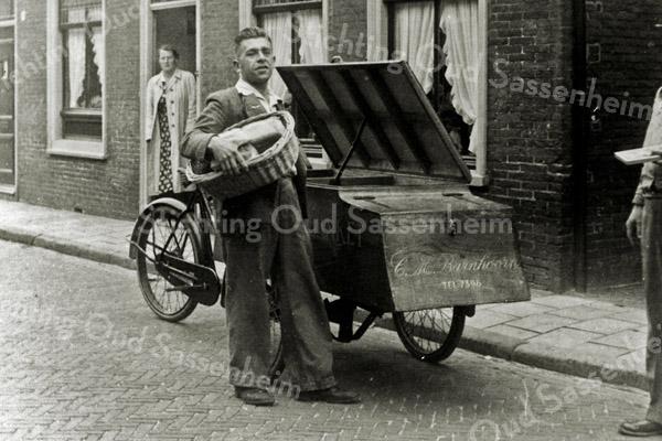 F0574 <br /> Bram Barnhoorn met bakfiets in de Kerklaan. In de deur staat mevr. Mien van Waardenburg-van den Bosch. Foto: 1943-1944.