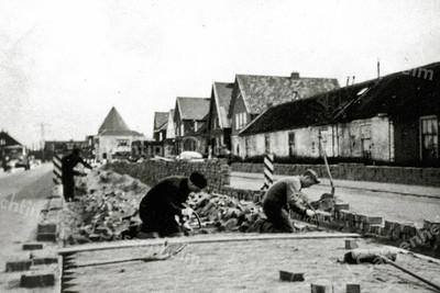 F0082 <br /> Herbestrating van de Hoofdstraat ter hoogte van 'de Zevenhuizen'. Dit gebeurde i.v.m. het verwijderen van de tramrails in 1950/1951. Sinds die tijd rijden er bussen voor het vervoer tussen Leiden en Haarlem. De persoon links is Lammert Visscher sr. (geb. 10-1-1889) en rechts Lammert Visscher jr. (geb. 2-3-1917). Foto: 1950/1951.